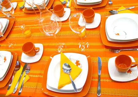 Modern plates, cups, glasses on orange table Stock Photo - 4539808