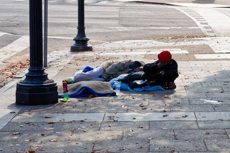Washington, D.C., USA - November 13, 2017: Two homeless African Americans are lying on the street in downtown Washington, D.C.
