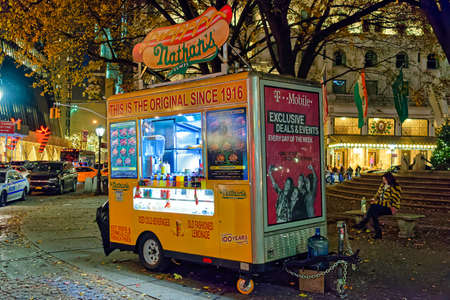 New York City, USA - December 2, 2017: The traditional street food cart selling hot dogs, french fries and beverages on a street corner in New York City.