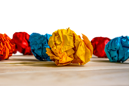 Balls of crumpled colored paper on a wooden table