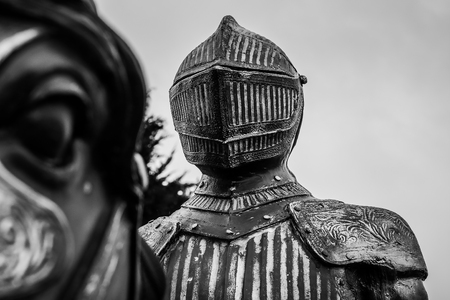 Black and white picture of a knight in armor who rides on the horse