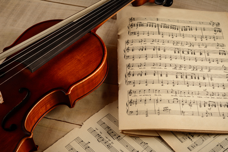 The violin and sheets with notes lie on a wooden table