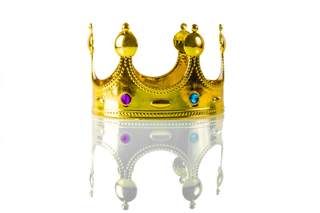 A golden crown with green and purple stones lies on a white background