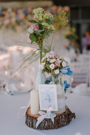 Wedding table decoration with candles and rose bouquets