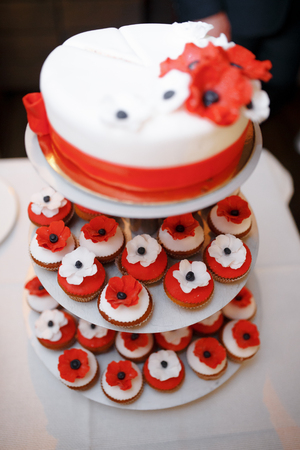 wedding feast: Vertical shot of a red and white wedding cake with small cupcakes decoration