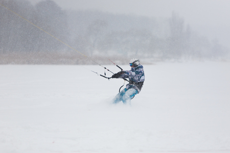 snowkiting: Kite surfer being pulled by his kite across the snow