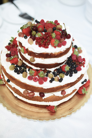 Vertical shot of a rustic style  wedding cake with fresh berries decoration