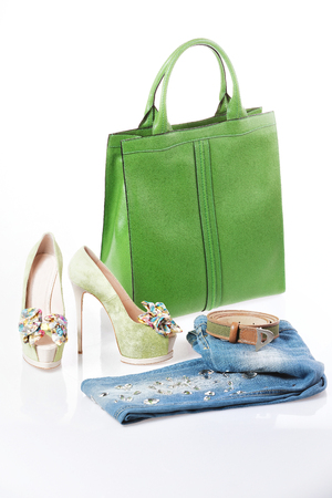 Jeans, green sandals and green leather handbag isolated