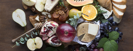 Variety of fresh fruits, sweets and cheeses shot from above an wooden board