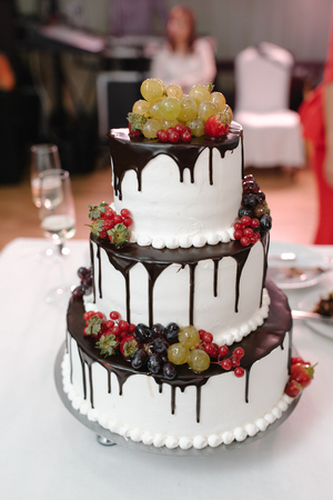 Vertical shot of a black and white wedding cake with fresh strawberries decoration