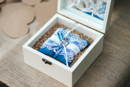 Wooden box with wedding rings on a blue pillow