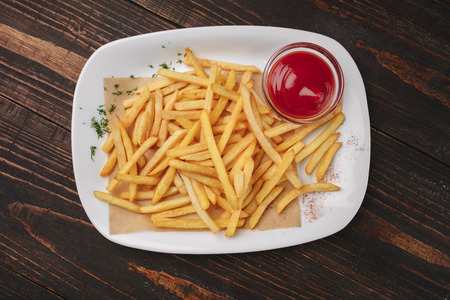 Beer snack - fried potatoes with ketchup on a white plate