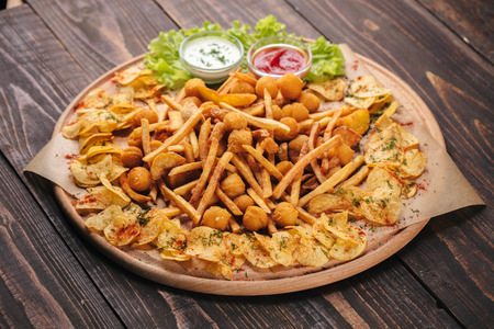 Big wooden tray with different types of fried potatoes and sauces