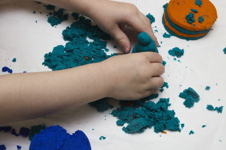 Childrens hands molded from colored sand