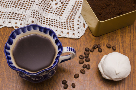 Coffee beans, ground coffee, white marshmallow and cup of brewed coffee on wooden table