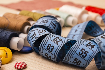 Blue measuring tape, buttons and multicolored thread spools 版權商用圖片