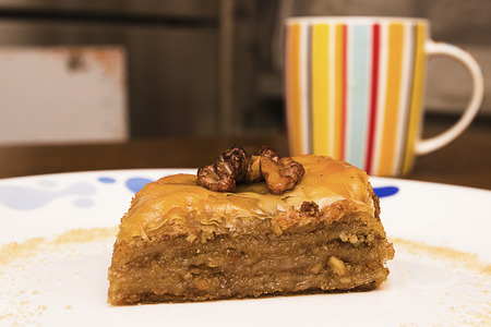 Baklava on a white plate, cup with tea