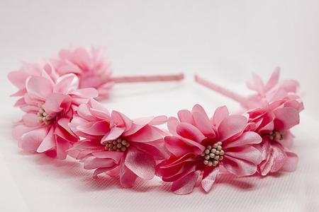 Baby hair accessory with pink flowers on white background