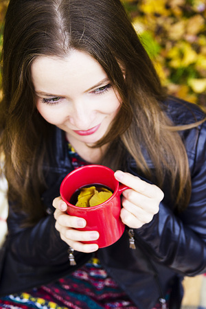 Beautiful young brunette girl drinks coffee in the park. Portrait in the autumn park. 免版税图像