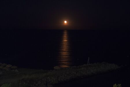 Full moon setting on the horizon in the ocean with reflection shining through Imagens