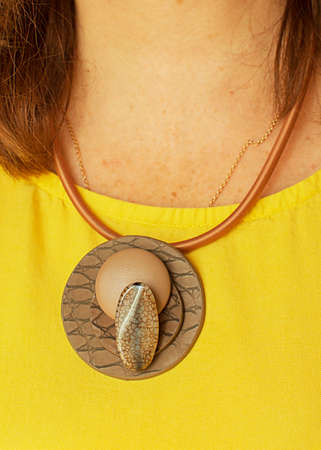 Brown code on the neck of a girl in a yellow dress. Decoration for the neck. Fashion. Stok Fotoğraf