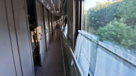 The corridor of the railway carriage is comfort class, windows on one side and compartments on the other.