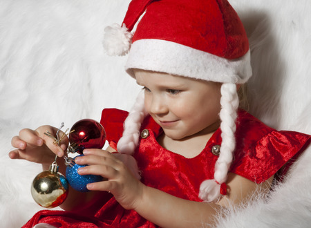 little child in christmas hat with christmas tree decorations photo