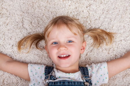 pretty eyes: happy smiling cute kid girl lying on white carpet and looking at camera