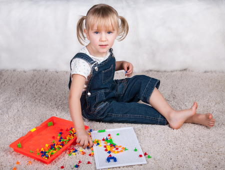 assiduous: little girl playing with education mosaic pins toy