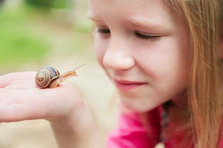 Hermosa niña rubia mirando y sosteniendo caracoles en su mano
