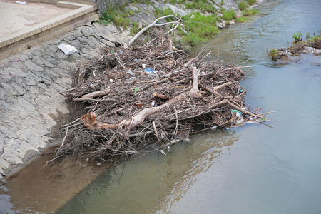 Plastic and wooden garbage in the river , pollution and environment concept. Stock Photo