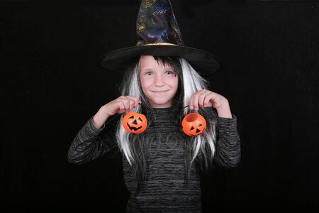 happy laughing child girl in witch costume with Halloween pumpkin candy jar on black background.