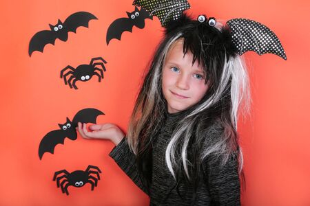 laughing child girl with pumpkins in witch costume on Halloween party. Halloween celebration concept, orange scary background with spiders and bats.