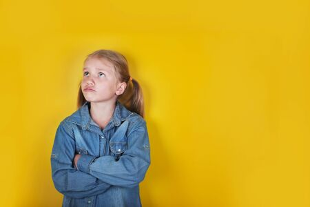 Little funny girl dressed in blue jeans shirt standing with arms folded on yellow background. Children emotions and expressions concept.