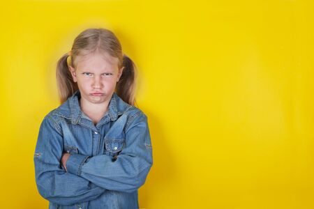 Niña divertida vestida con camisa de jeans azul de pie con los brazos cruzados sobre fondo amarillo. Concepto de emociones y expresiones de los niños.
