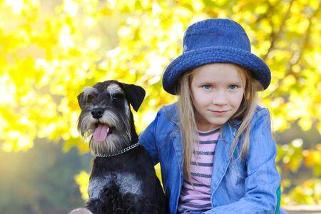 Child blond girl lovingly embraces his puppy pet schnauzer dog. Friendship. Autumn colors. Stockfoto