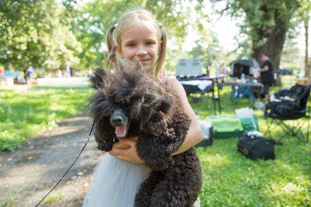Child blond girl lovingly embraces his puppy pet Poodle dog. Friendship.