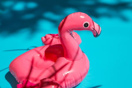 Pink flamingo swim ring drink holder on turquoise background with shadows of exotic plants. Summer , vacation concept
