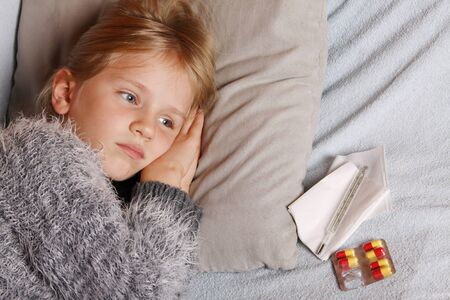 Sick little girl lying in bed with a thermometer and medicine Standard-Bild