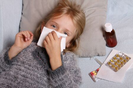 Sick little girl lying in bed with a thermometer and medicine