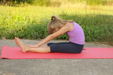 Little blond girl doing fitness yoga stratching exercises in the park