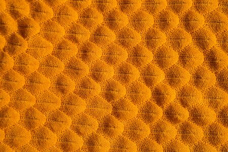Orange knitted fabric background. Close up gray fabric texture background. wrinkled and shadows, selective focus top view.