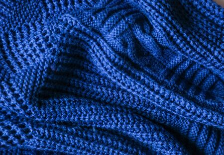 Classic blue dark knitted background. Close up texture . wrinkled and shadows, top view. 2020 trend color.