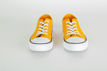 Stylish yellow sneakers shoes with white shoelaces on white background Stockfoto