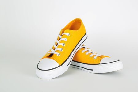 Stylish yellow sneakers shoes on white background
