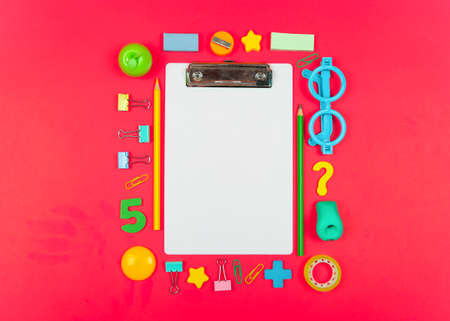 Back to school shopping concept. Colorfull School supplies on red background. Flat lay, top view, copy space.
