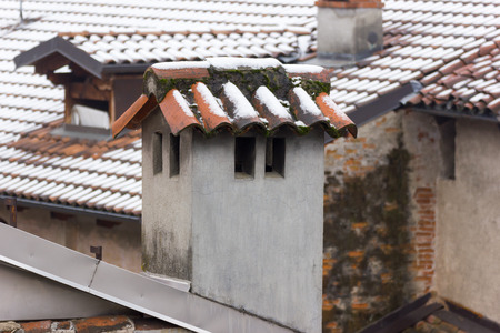 cement chimney: tiles and a concrete chimney with snow
