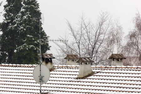 gas fireplace: Four concrete chimneys covered by snow, full of shingles, and the roof covered with snow Stock Photo