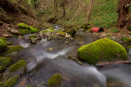 little creek scenery with metal bin in long exposure Banco de Imagens