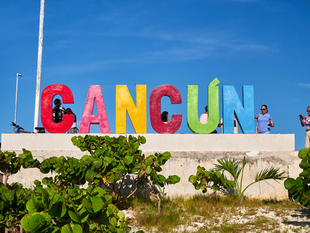 Tourists in front of the sign of Cancun, Playa Delfines, Mexico, in September 7, 2018